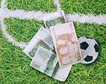 ein Fußball und Geldscheine auf Fußballplatz