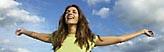 Bildmarke Suchtprävention - Eine junge Frau, lachend und mit ausgebreiteten Armen, im Hintergrund ist der Himmel zu sehen