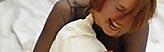 Bildmarke Frauengesundheit - Eine junge, lachende Frau, mit einem Kopfkissen im Arm