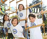 """Eine Gruppe Kinder an Kletterseilen mit """"Kinder stark machen"""" Shirts"""